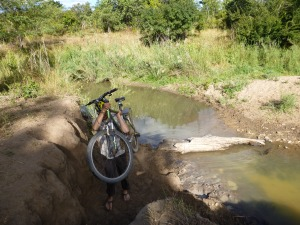 Samwell hoisting his bike up over a steeply eroded stream bank.