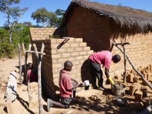 Boyd helping Ba Chilando lay bricks.