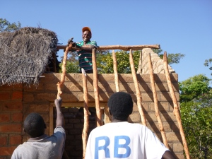Ba Bernardi and Ba Abraham pass poles up to Ba Ronaldi while building the roof to my tool shed.