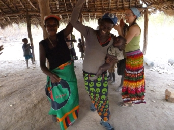 """Sisters Ba Lister and Ba Judith dancing with """"stolen"""" baseball caps at """"American Culture Day"""" in Mfuba."""