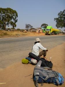 Samuel waitin' for a ride in the dust outside Serenje.