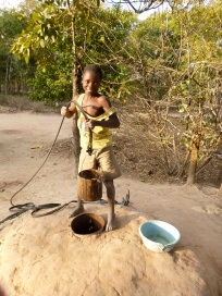 Bwalya fetching water at his family's well.