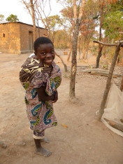Loyci with baby brother Musonda on her back.