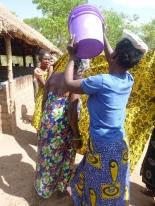 Ba Nellis dumping water on Ba Priscilla as part of a wedding ceremony for Ba Priscilla.