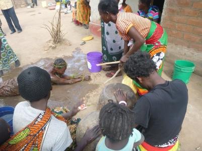 Ba Priscilla rolling on the muddy ground as part of her village wedding.