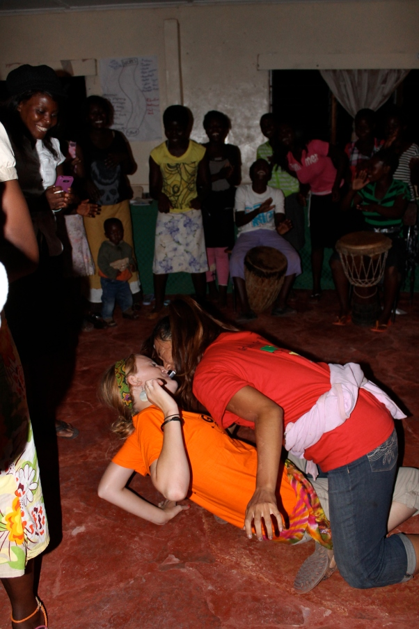 """Then PCVs Jasmine and Clara gave the dance a try. Clara, acting as the """"man,"""" had to get the token out of Jasmine's mouth - using only HER mouth. The Zambians loved this!"""
