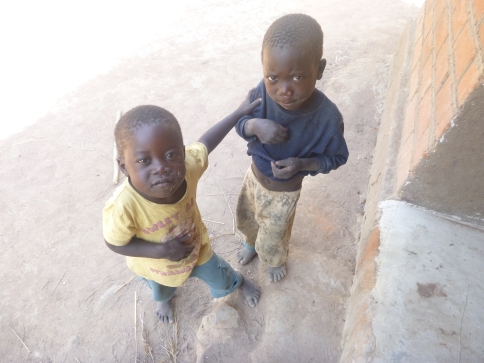 Agri and Katongo, eating dried caterpillars (in Katongo's shirt) at my front door.