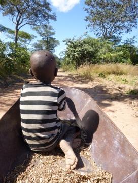 Katongo riding in a borrowed wheelbarrow on the way back from my field.