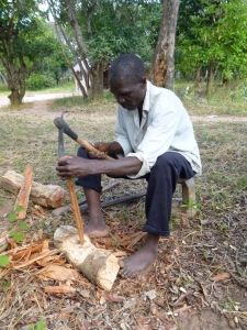 Ba Allan Mwango carving wooden cooking sticks. He owns a few pairs of shoes, but rarely wears them around the house.