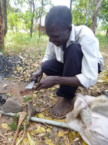 Ba Allan Mwango puts the final touches on the wooden cooking spoons he makes. The plastic bellows at right is what stokes the fire to heat his metal tools.