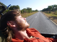 Adam enjoying the sunshine and open-air transport from the back of a pick-up truck on the Mansa Road.