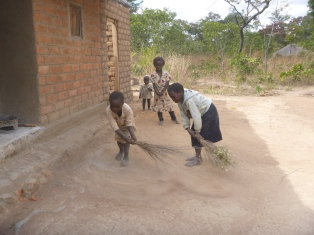 """""""Iwe! Sweep my yard!"""" Young girls like Cila (left) and Joyci get no respect in Bemba. But they really seem to love helping out around the house."""