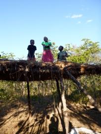Maria, Chola, and Katongo atop a big groundnut drying rack