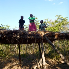Maria, Chola, and Katongo atop a big groundnut drying rack