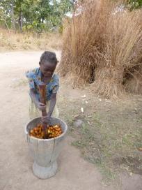 Norida pounding mpundu fruits in her family's ibende (mortar).
