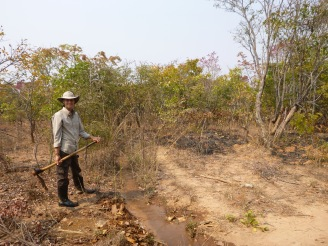 Samuel opening up his leaf-choked furrow to water his fields.