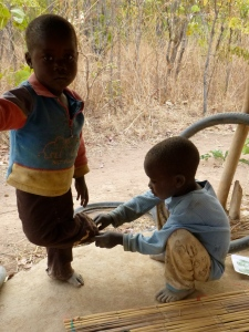 Katongo getting a splinter out of his little brother Agri's foot.