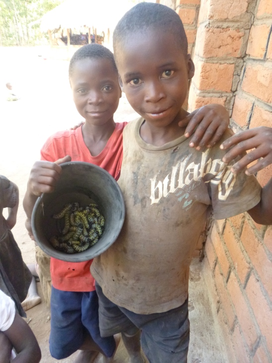 Bwalya poses with a new friend, who came to Mfuba with his family to harvest caterpillars.