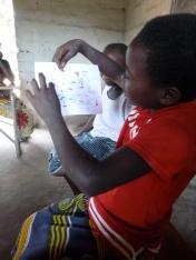 Joyci explains her drawing of her future aspirations, at an Mfuba GLOW Club meeting.