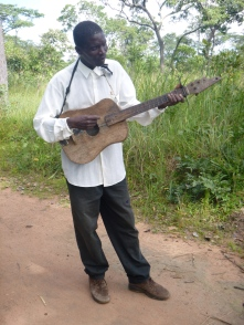"Ba Allan, trying unsuccessfully to play the bush guitar. (""Bush"" because it's homemade.)"