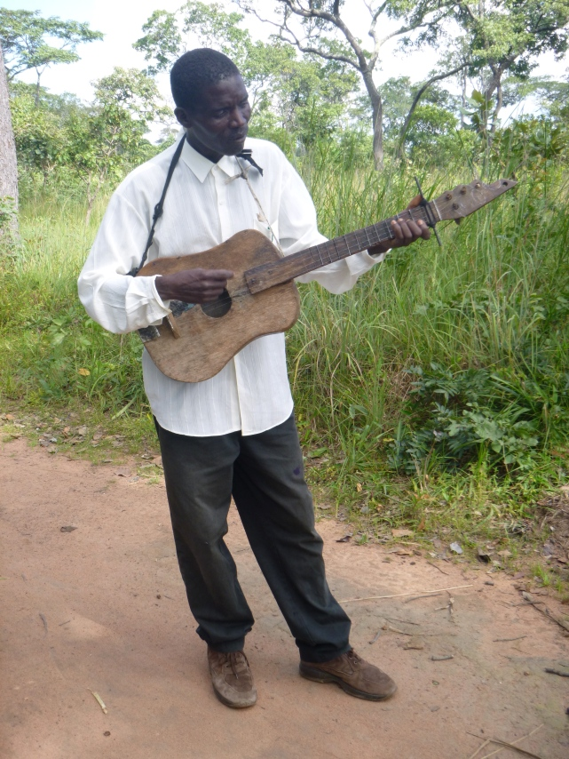 """Ba Allan, trying unsuccessfully to play the bush guitar. (""""Bush"""" because it's homemade.)"""