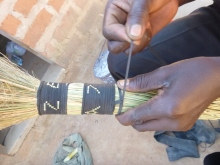Mwila making a broom from dried grasses and sliced up bits of bike tubing.