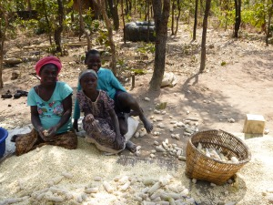 Ba Scolastica with two of her kids, Charles and Loyci, shelling maize.