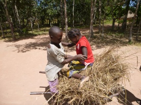 Bwalya helping Joyci into the communal wheelbarrow.