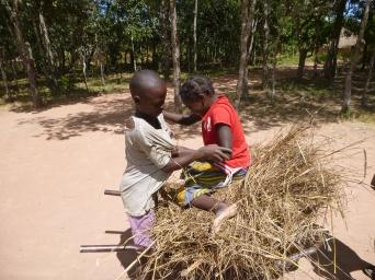 Bwalya helping Joyci into the communal wheelbarrow.