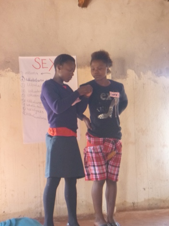 Elizabeth and Given perform a skit in front of the group.