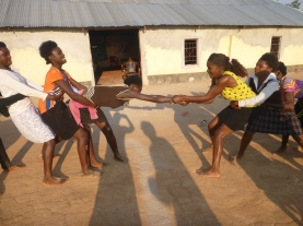 One of our Zambian facilitators, Maggie, drags one of the girls relentlessly across the center line in a human tug-of-war.
