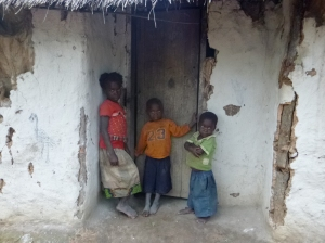 Katongo and Agri - along with their aunt Naomi - in the doorway of the home they just left.