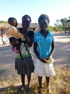 GLOW girl Muso, left, holding someones baby and standing with her friend Cynthia.