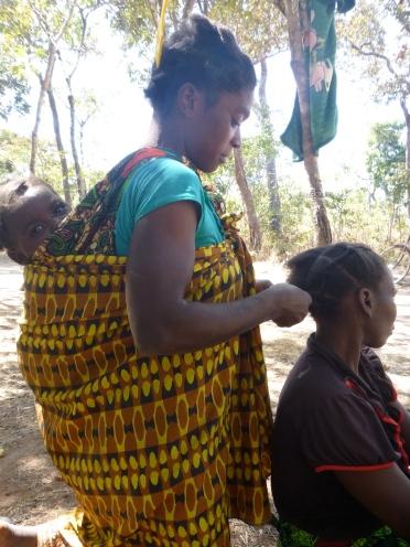 Ba Scolastica braids Ba Agatha's hair while her baby, Musonda, checks out the camerawoman.
