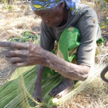 Banakulu Teba weaving wetland grasses into a broom.