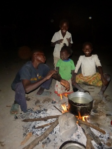 Four of the Mutale kids around their evening fire: Boyd, Gile, and Cila up front, with Joyci in the background.