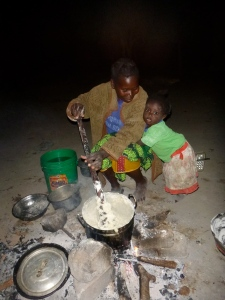 Ba Agatha talking with her daughter Gile while cooking ubwali over a traditional three-stone fire.