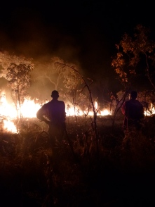 Ba Allan and Ba Bernardi watch the fire they started to make a firebreak around the Mfuba Co-op's field.