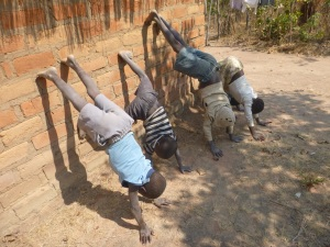 Kamfwa, Katongo, Muso, and Cila all trying to do hand stands against the back wall of my house.