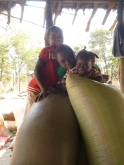 Joyci, Stephen, and Gile goofing around atop some maize sacks in their family's nsaka.