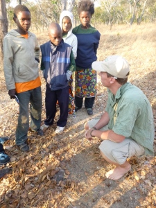 Bastiaan points out a hippo footprint to Kingsley, Stephen, Gertrude, and Cynthia.