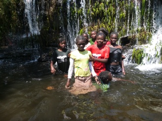Girls of Camp TREE playing under the waterfall.
