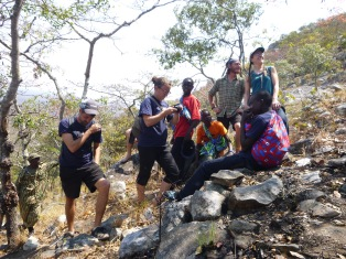 Taking a break on the way up Mount Lavushi: Trevor, Taylor, Cornelius, Kingsley (seated), Adam, me, and Golden (seated, with the red icitenge backpack).