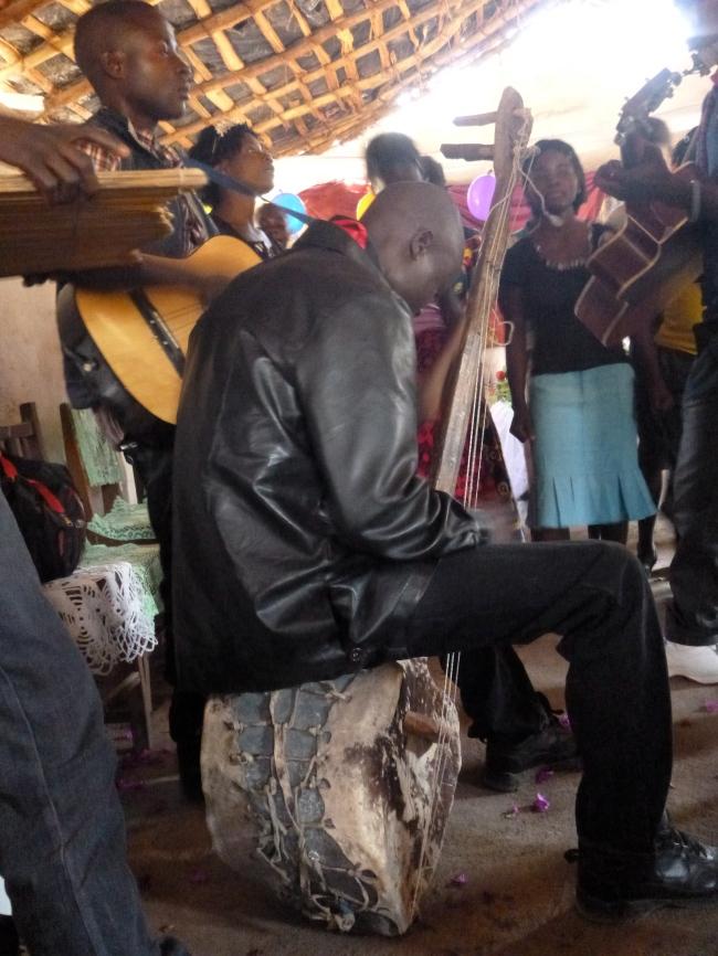 """Man playing a hand-made """"bush bass"""" at a wedding in Chisamba."""