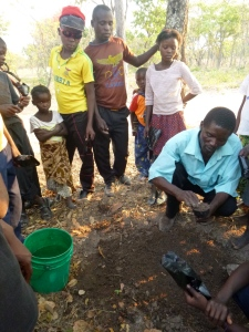 Ba Allan teaching our Grassroots Soccer HIV/gender club how to plant moringa trees.