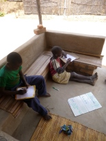 Stephen and Allan Jr. patiently copying down the day's English lesson.