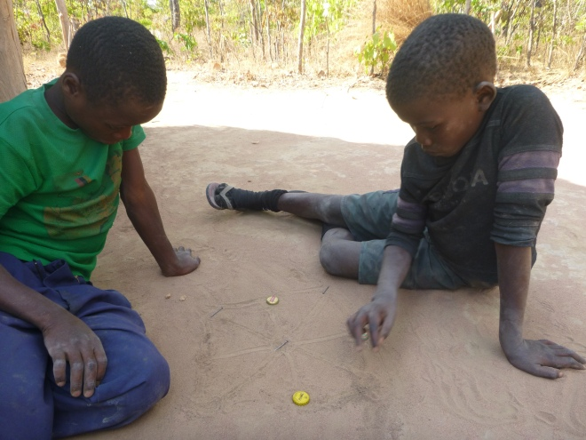 Stephen and Allan Jr. playing a homemade strategy game with bottle caps and nails.