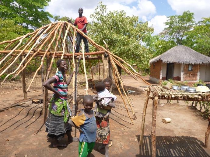 Bana Kessia and Bashi Kessia (up top) building a new nsaka at their home.