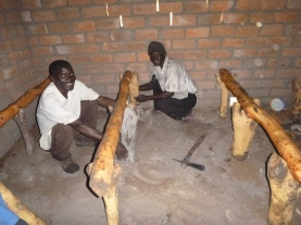 Ba Allan and Ba Abel working on a raised-platform goat shelter.