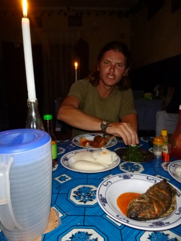 """Adam eating our """"last supper"""" of the trip, in Mporokoso. It wasn't a romantic dinner; the restaurant had just lost power."""